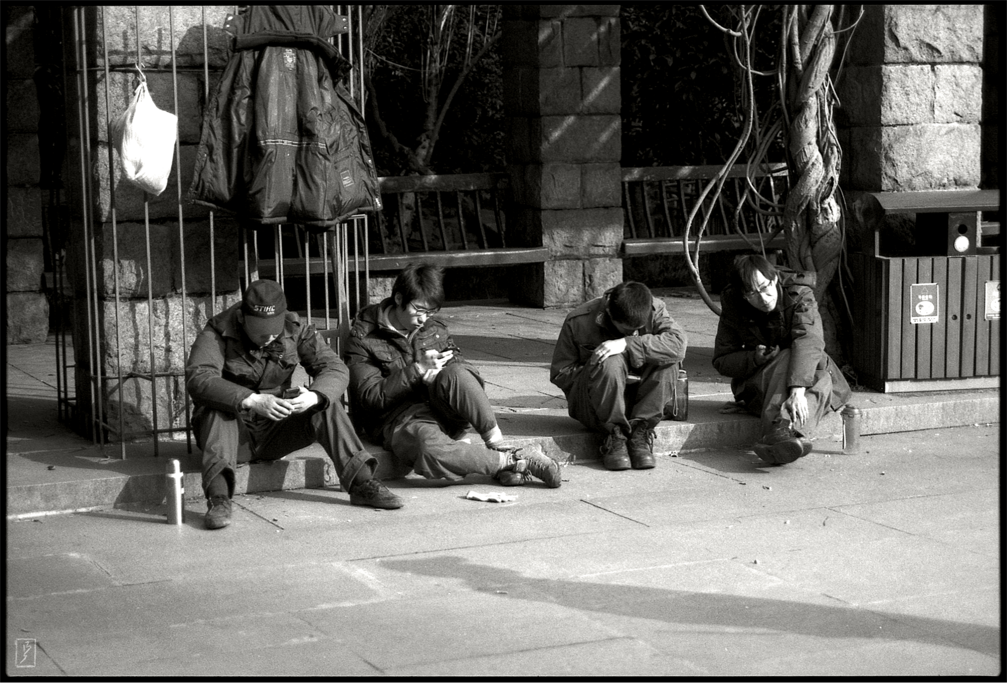 Lu Xun park (): Young gardeners on a break using their smartphones.